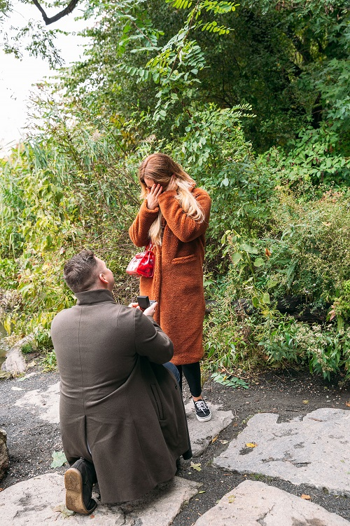 Girlfriend covers face as boyfriend proposes on one knee Central Park