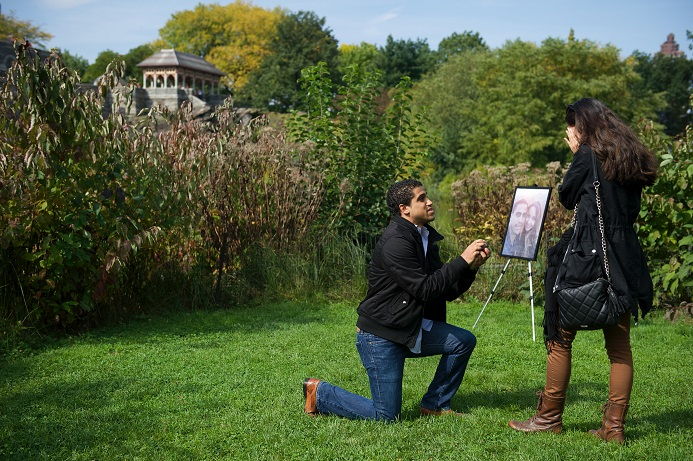 Boyfriend proposes in Central Park with portrait of couple on an easel in background