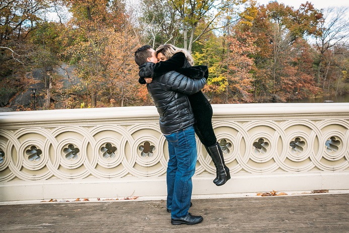 Man hugs woman and lifts her off feet on Bow Bridge after marriage proposal