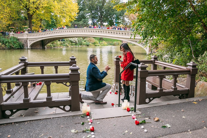 Man down on one knee proposing to girlfriend on decorated landing Bow Bridge