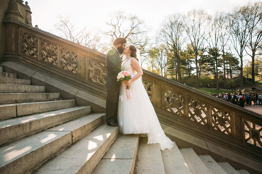 Bride and Groom kiss on stairs of Bethesda Fountain in Central Park