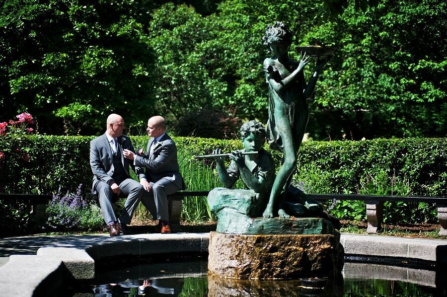 Gay couple poses by fountain in South Garden on sunny day