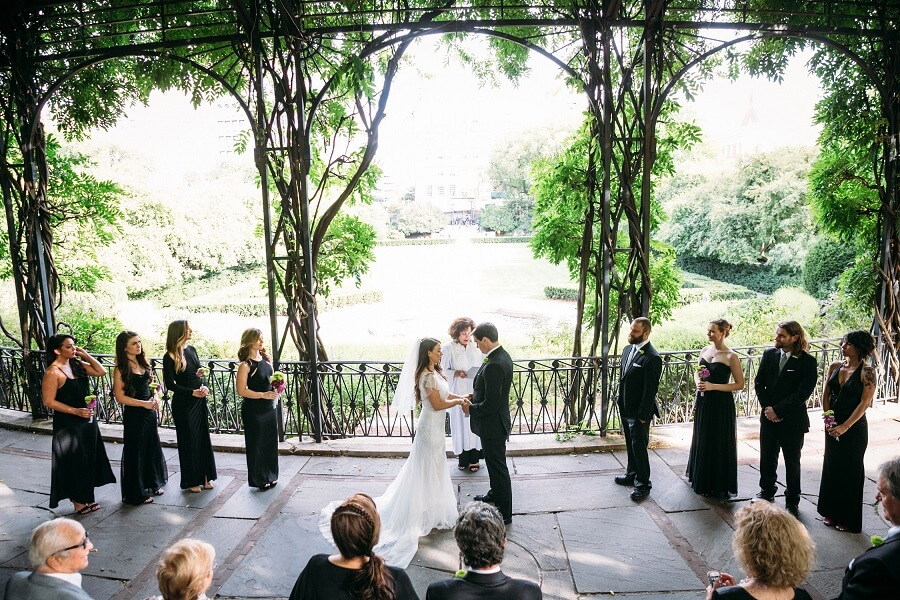 Couple holds hands during intimate wedding at the Wisteria Pergola