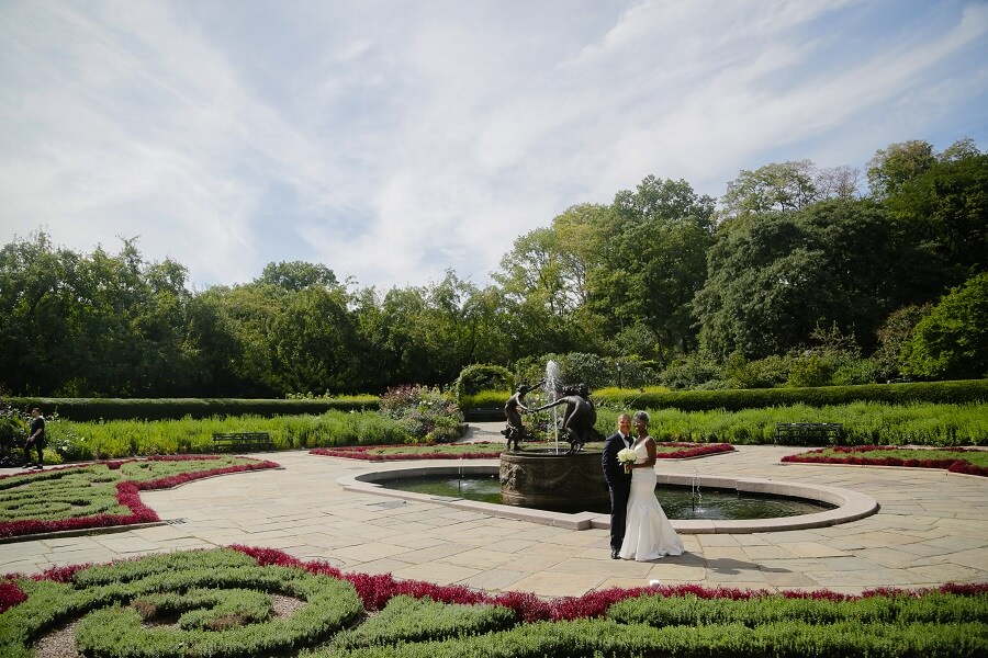 Wide shot of newlyweds posing in North Garden in Central Park