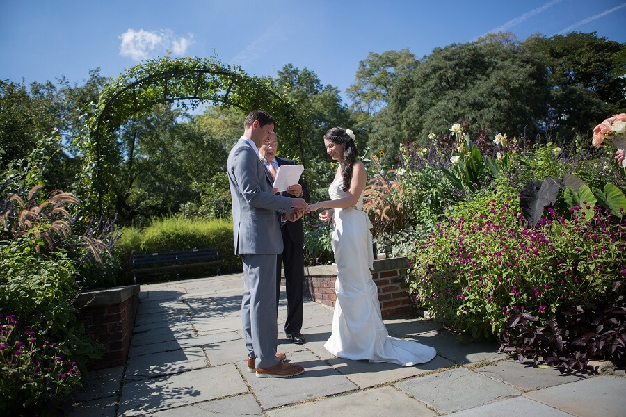 Couple exchanges ring in front of archway in North Garden in Central Park