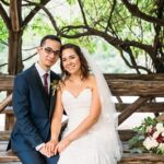 Bride and groom sit on wooden bench in Cop Cot