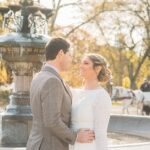 Bride looks at groom in front of Cherry Hill fountain in Fall