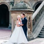 Newlyweds laugh by the Bethesda Fountain architecture