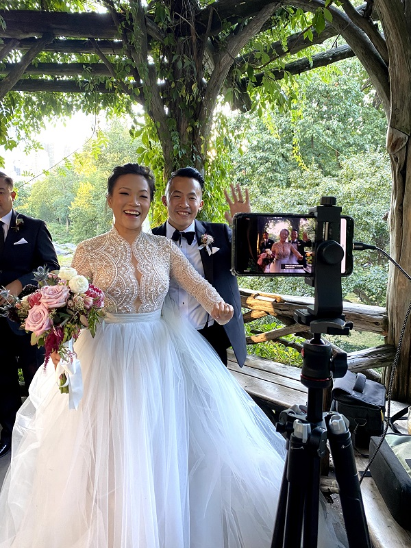 Bride and groom wave to virtual wedding guests