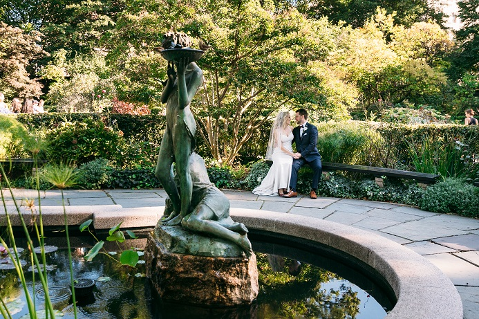 Bride and groom site on bench by Burnett fountain