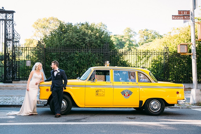 Bride and groom pose by vintage NYC checker cab