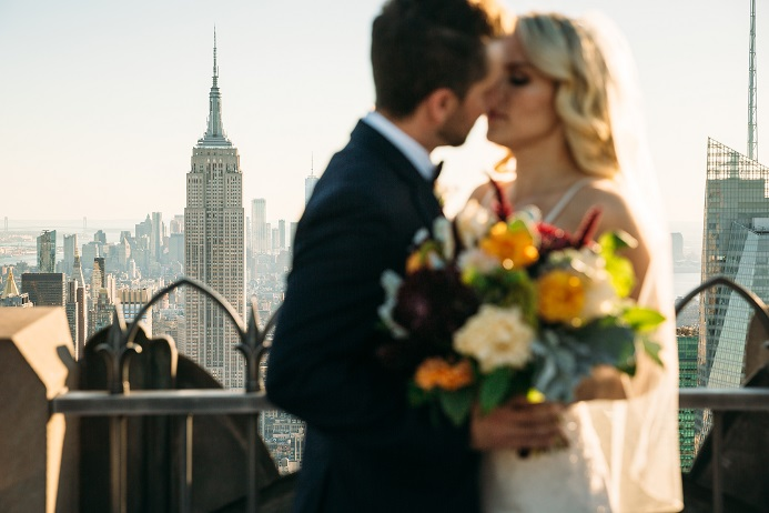 Newlyweds kissing with Empire State building in background