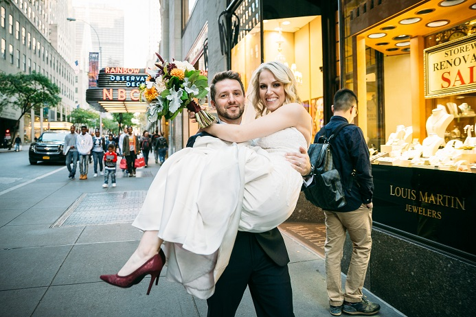 Groom carries bride through NYC streets