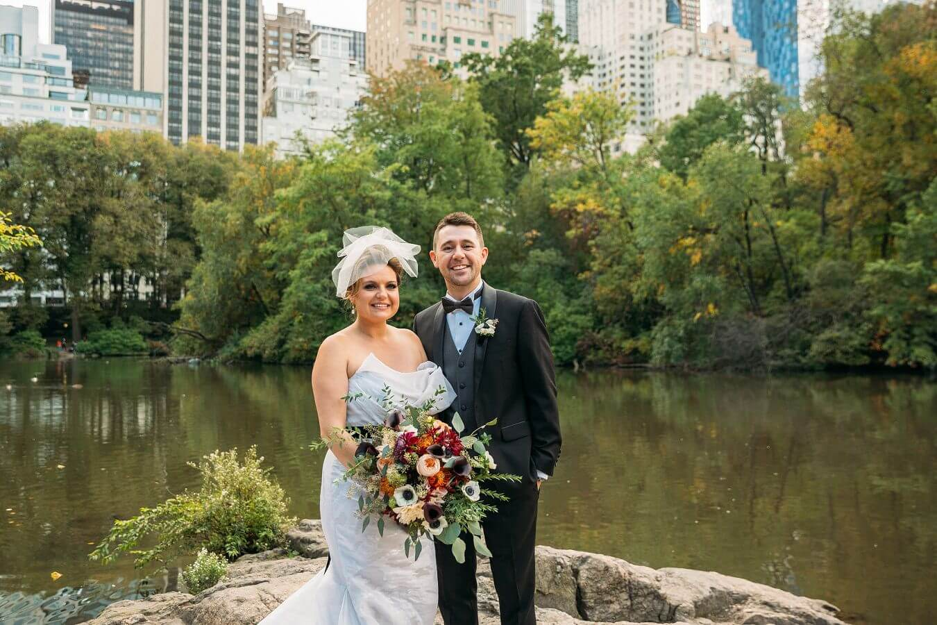 Wedding Couple poses by Gapstow Bridge with NYC Skyline