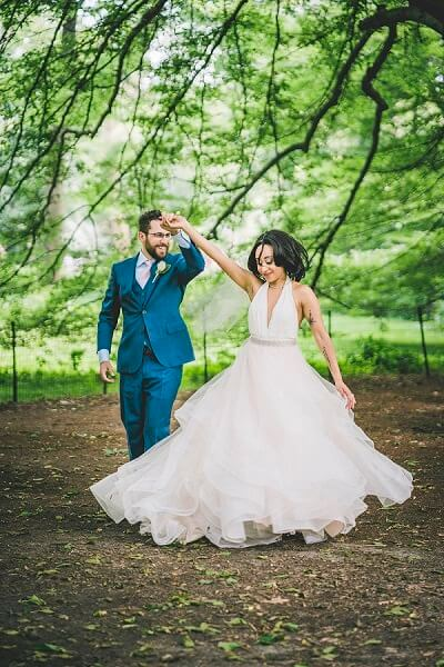 Groom twirls bride in Central Park