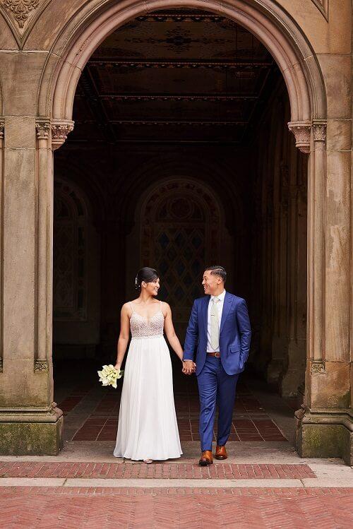 Wedding couple walks walks through arches at Bethesda Fountain