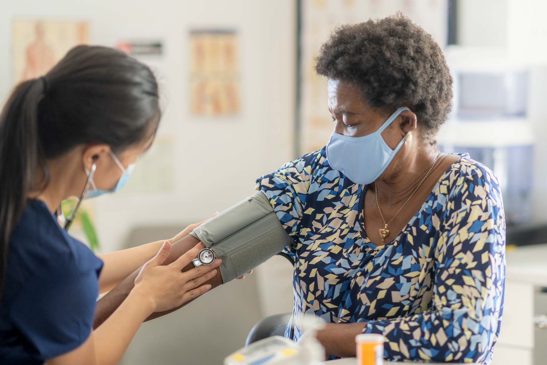 nurse taking blood pressure of woman