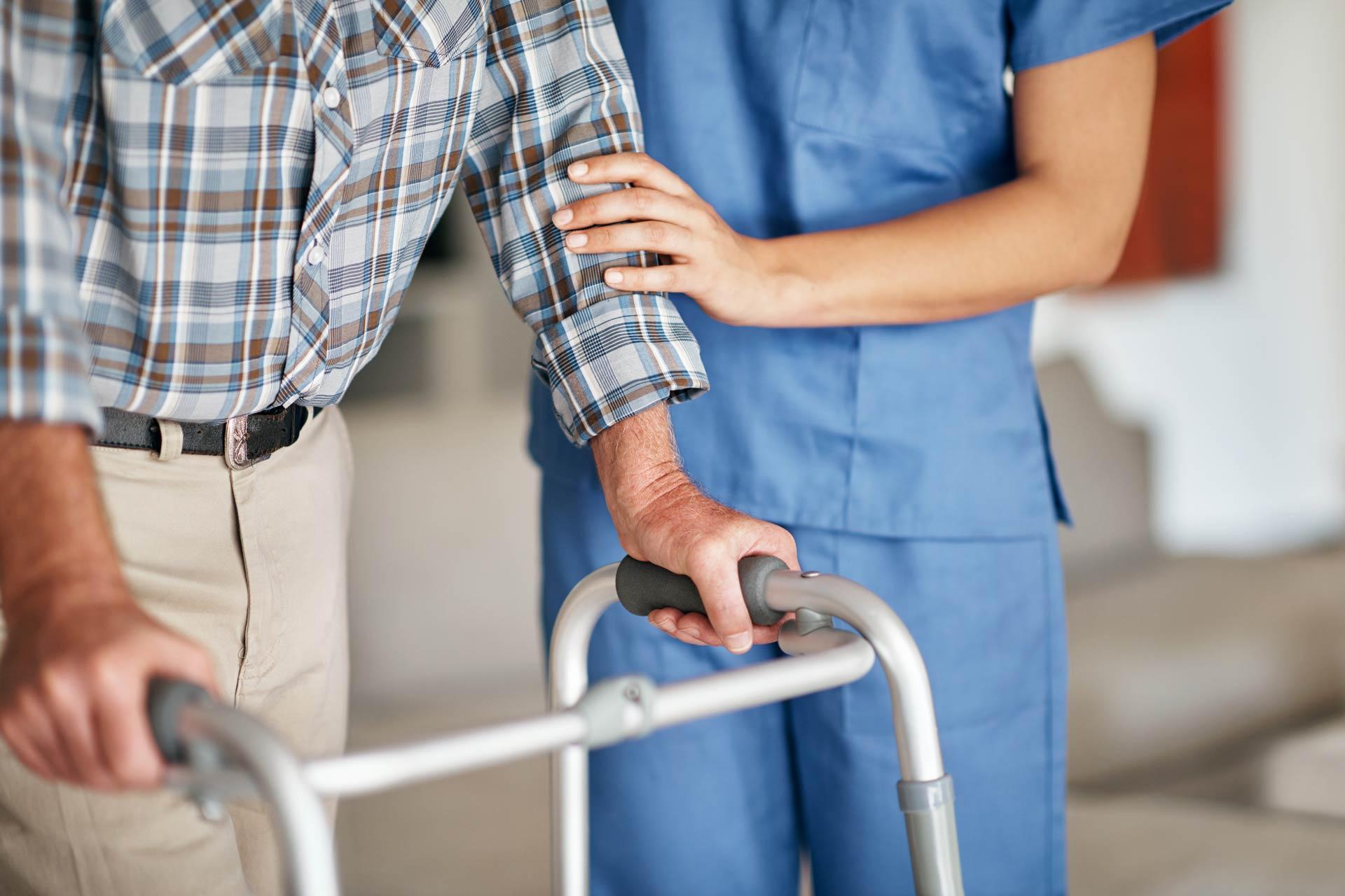 nurse helping elderly man on walker