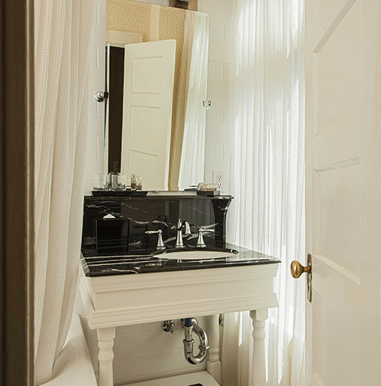 Ornate sink and countertop by a bathtub