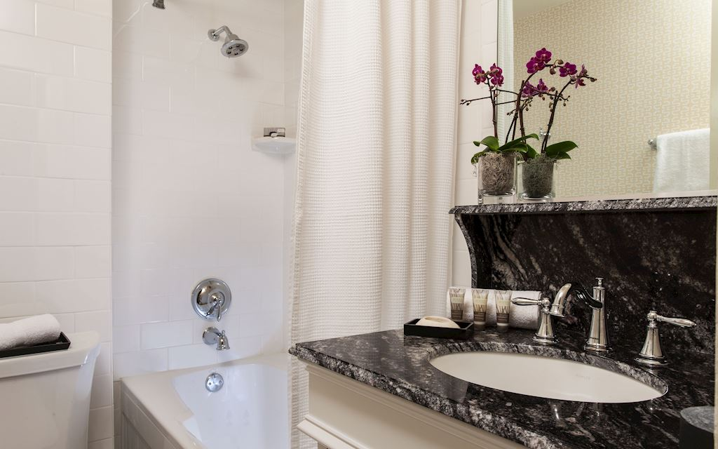 Curtained bathtub with a marble countertop and sink