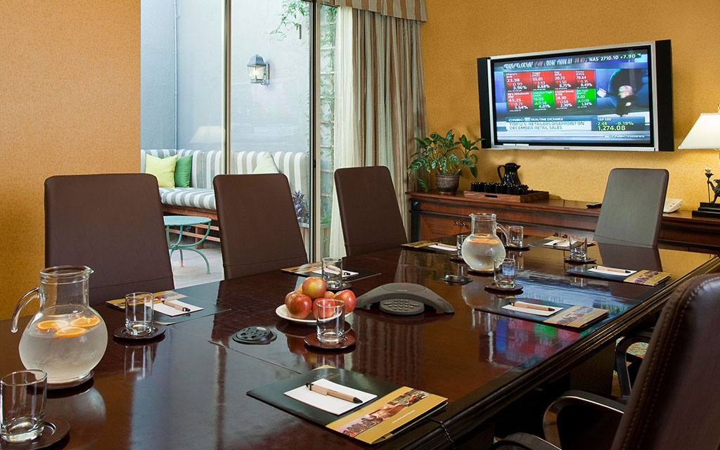 Conference table and chairs set for a meeting with a television on the far wall