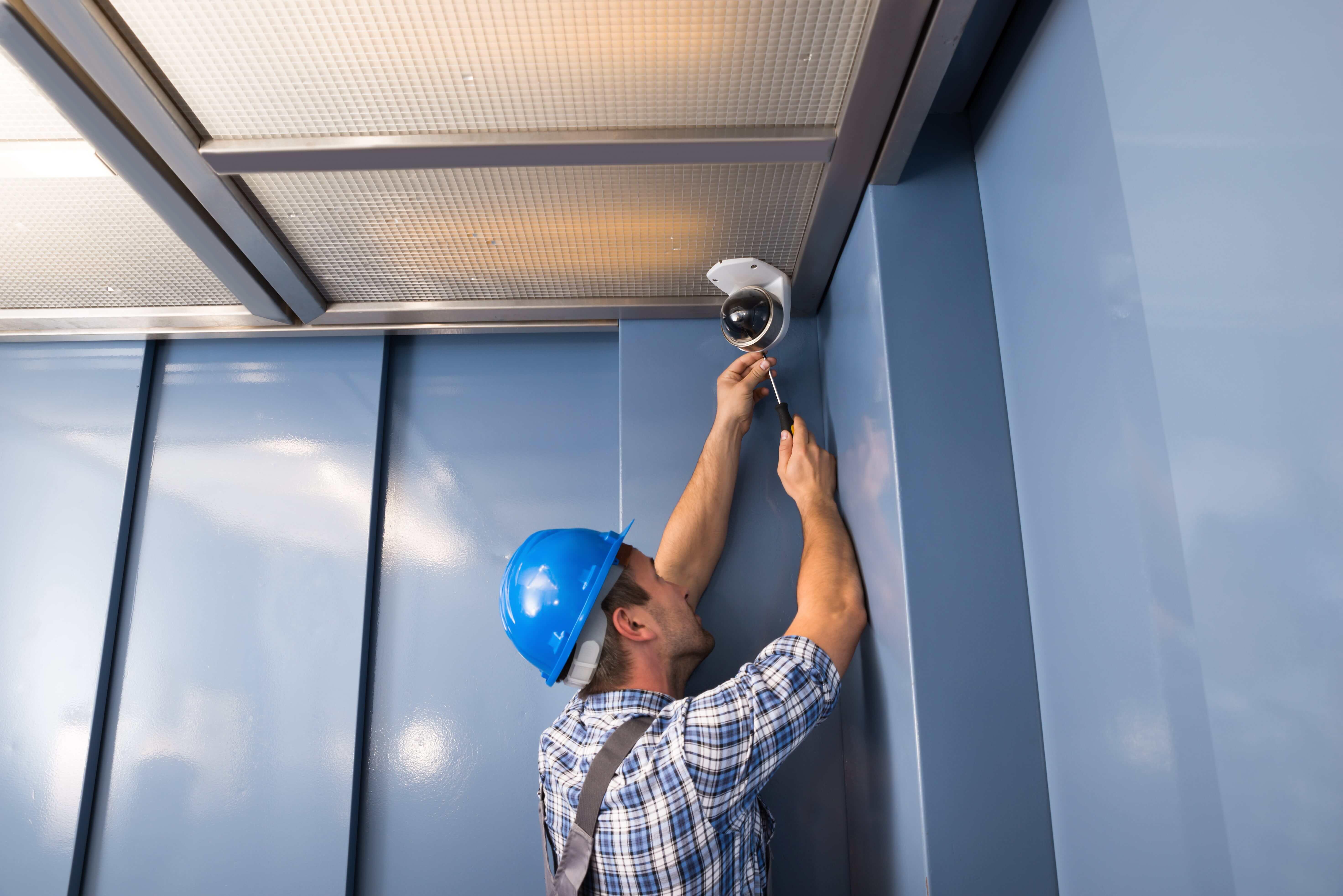 technician working on camera in elevator