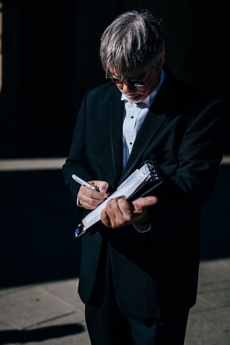 A photo of the officiant signing the marriage license just after the ceremony at Palace of Fine Arts San Francisco CA
