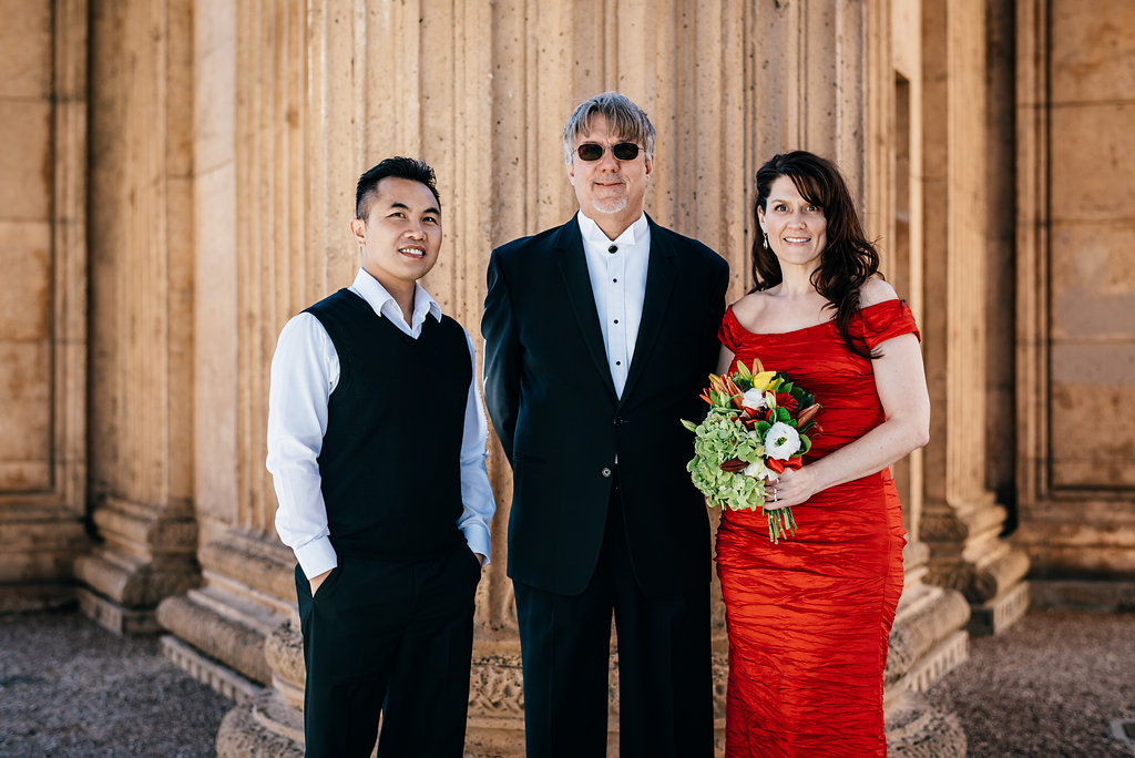 A photo of The officiant posing with the couple after the wedding at Palace of Fine Arts, San Francisco CA