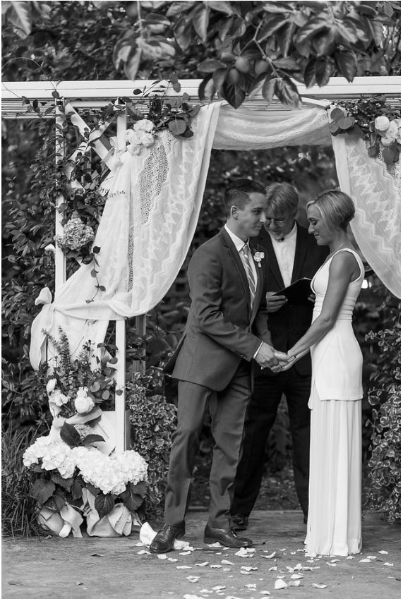 a black and white photo of the groom breaking the glass under the chuppah. at an Interfaith Wedding Ceremony held at the Marin Art & Garden Center in Ross, Marin County CA