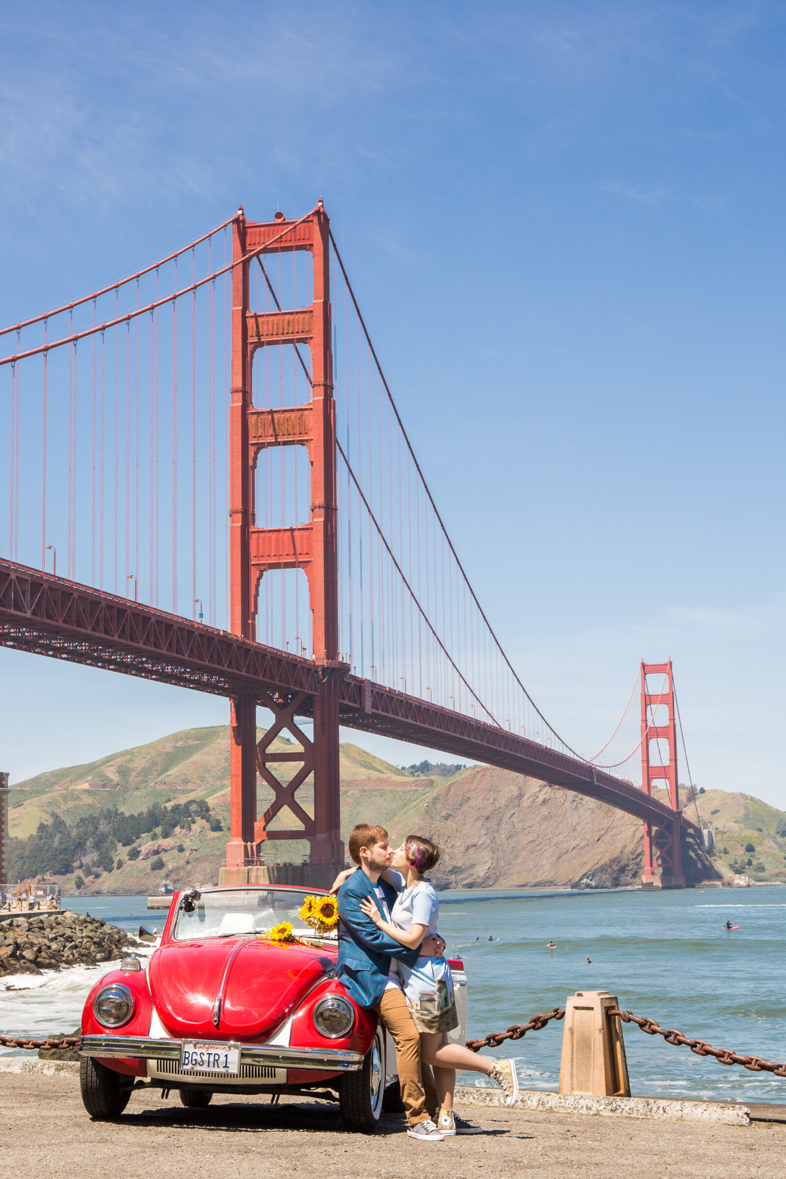 A photo of a couple with an old Volkswagen Bug convertible under the Golden Gate Bridge.