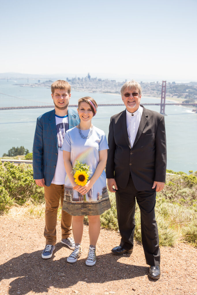 a photo of the Wedding Officiant with the couple in the Marin Headlands overlooking the Golden Gate. Photo by Dmitry Rogozhin, www.DmitryRogozhin.com
