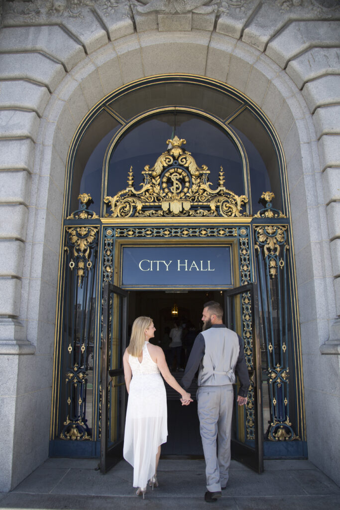 A photo of a couple at the entrance to San Francisco City Hall