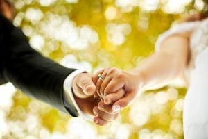 A photo of the hands of a newly married couple with prominent wedding ring