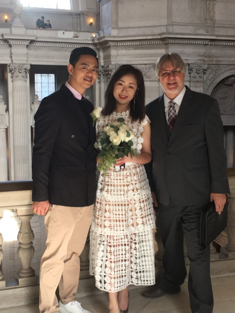 A photo of the Officiant posing with the couple on the third-floor balcony at San Francisco City Hall