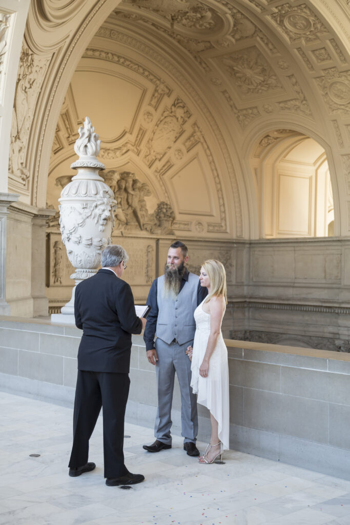 A photo of a couple and their Elopement fourth-floor balcony City Hall