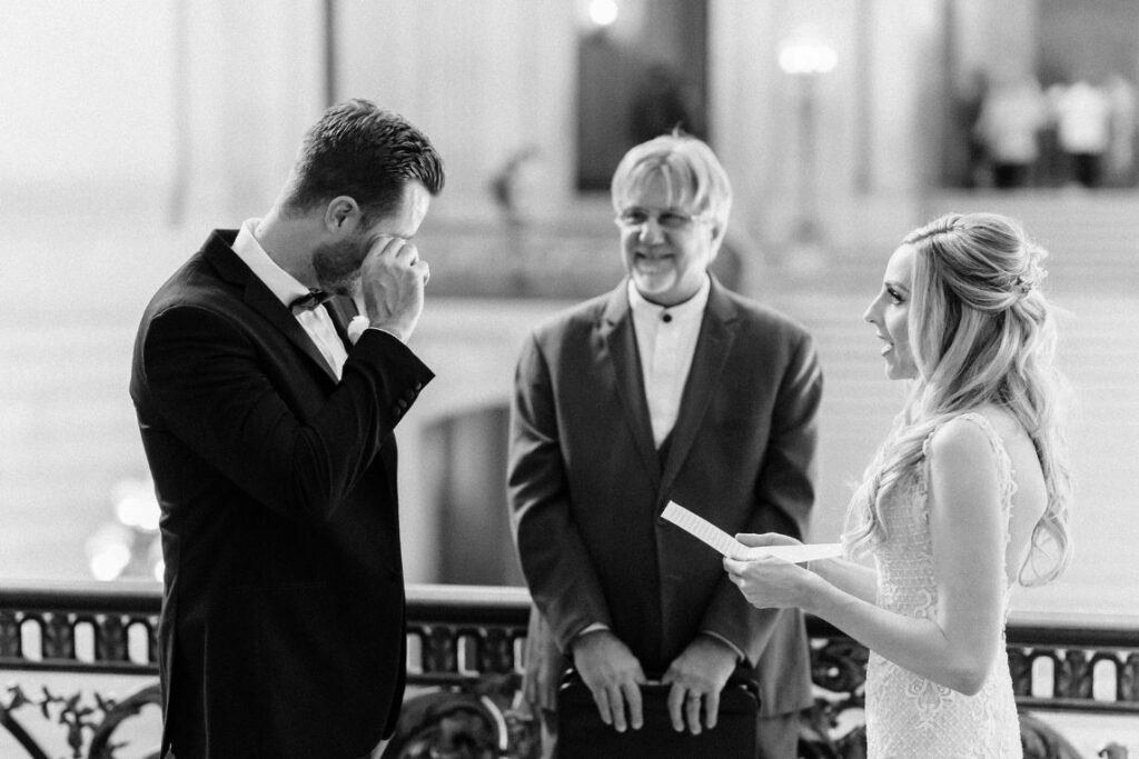 A photo of Bride reciting her wedding vows during a wedding on the Mayor's Balcony in San Francisco City Hall.