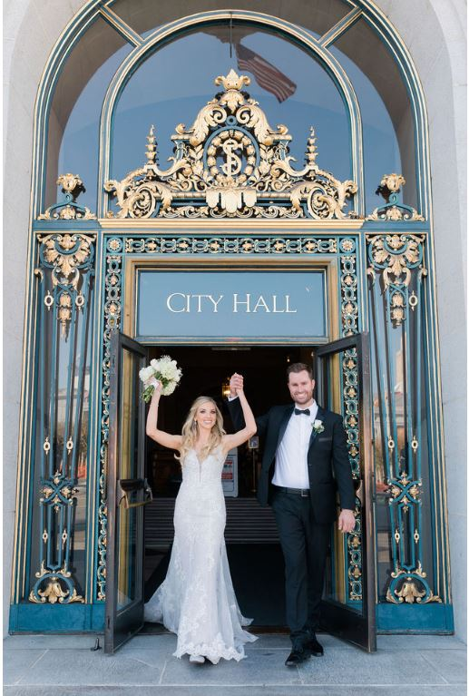 A photo of a couple Bride and Groom Celebrating their wedding at the entrance to San Francisco City Hall