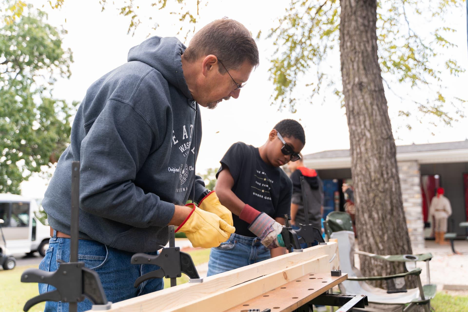 Men's Summit Activity. Man in gray sweatshirt teaching boy in black shirt how to work with wood