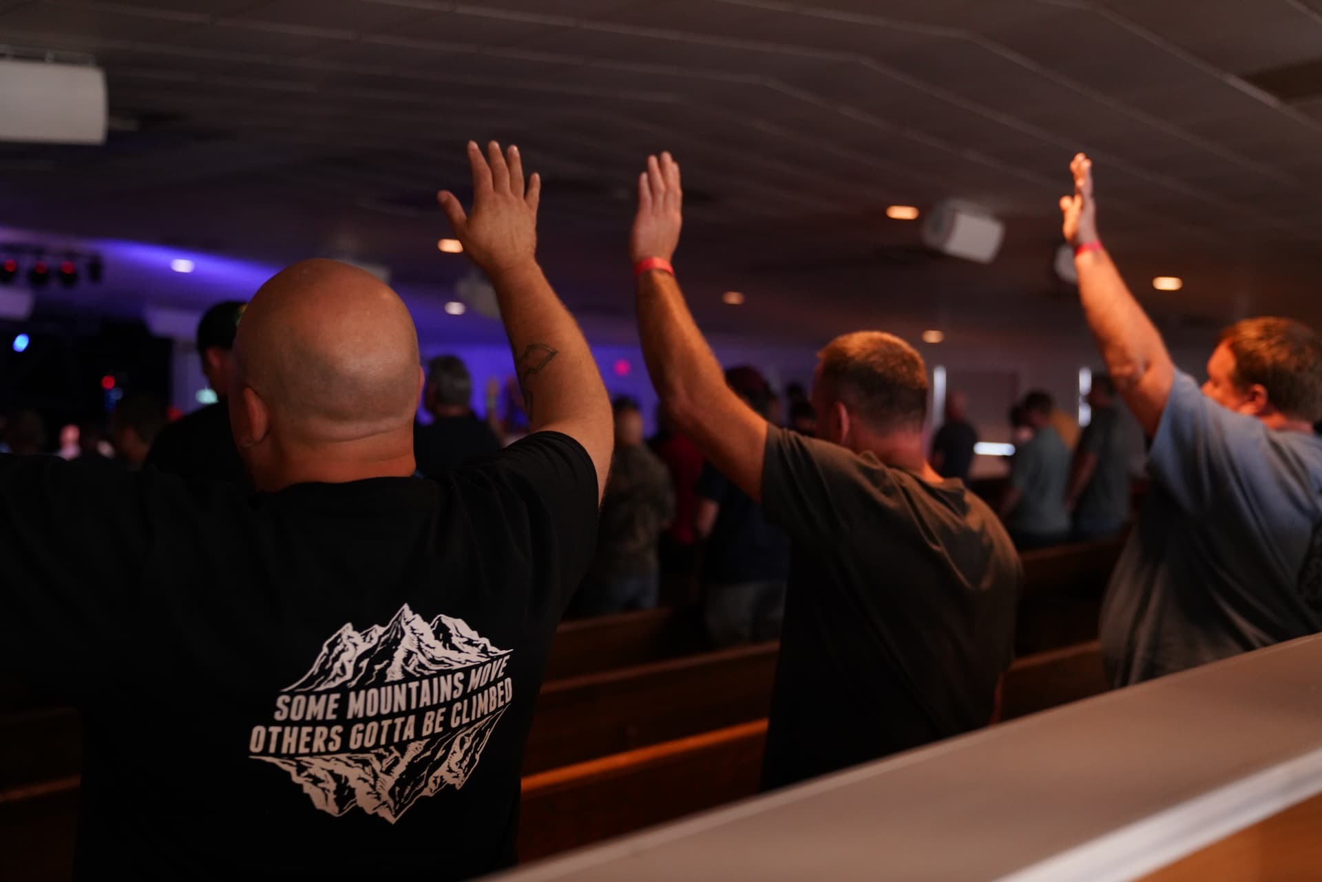Men's Summit Worship. Man with both arms lifted in worship. Band on stage in blurred background
