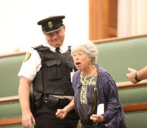 Two guards in the viewing gallery at Ontario legislature stand next to an older protesting woman before she is removed by force.