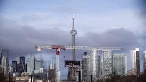 Toronto skyline with a giant construction crane and the CN Tower in the background.