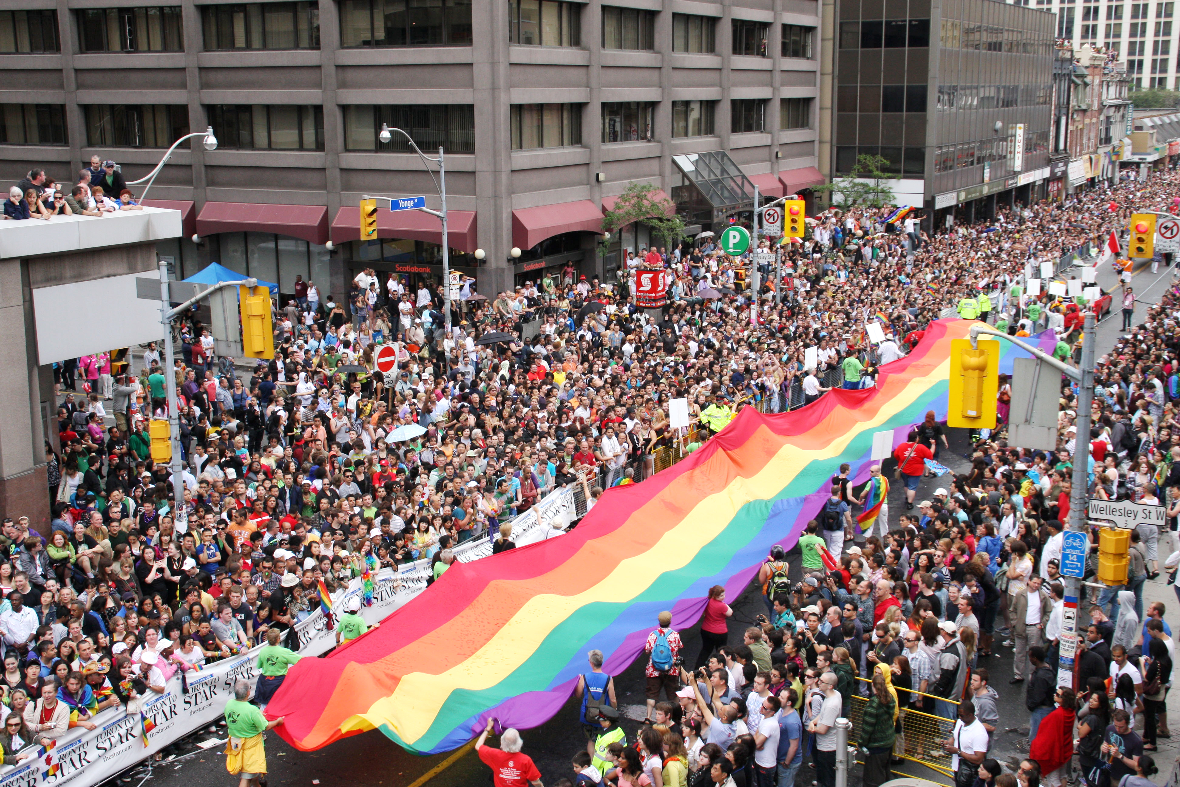 Image Description: Toronto Pride Parade with a long wide rainbow flag that stretches over 40 metres.