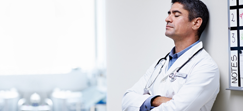 Doctor leaning against a wall with eyes closed and thinking.