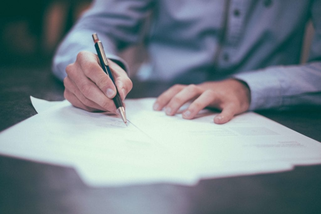 A photo of a man holding a pen signing some documents in Laguna Hills, CA.