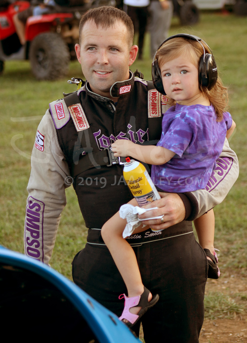 Crate late model racer Justin Smith, of Barbourville, Ky., holds his two-year-old daughter, Averie Grace, while applying detail spray prior to hot laps at Ponderosa Speedway in Junction City, Ky.