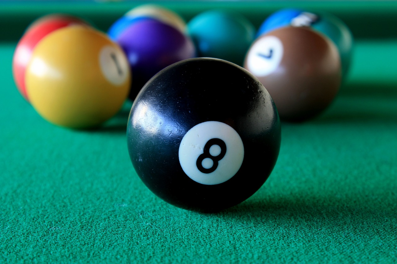 8 ball in front of other snooker balls on billiards table