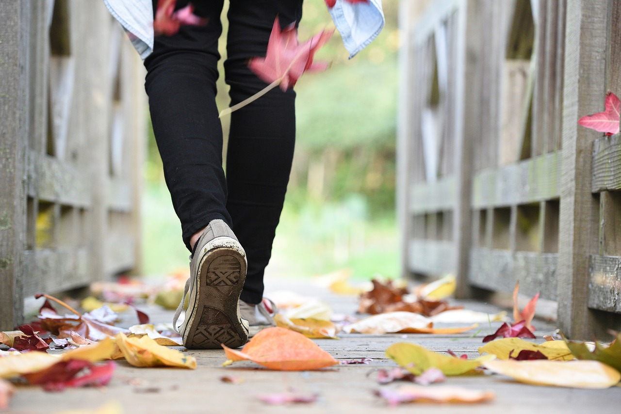 Person walking down a path with fall leaves.
