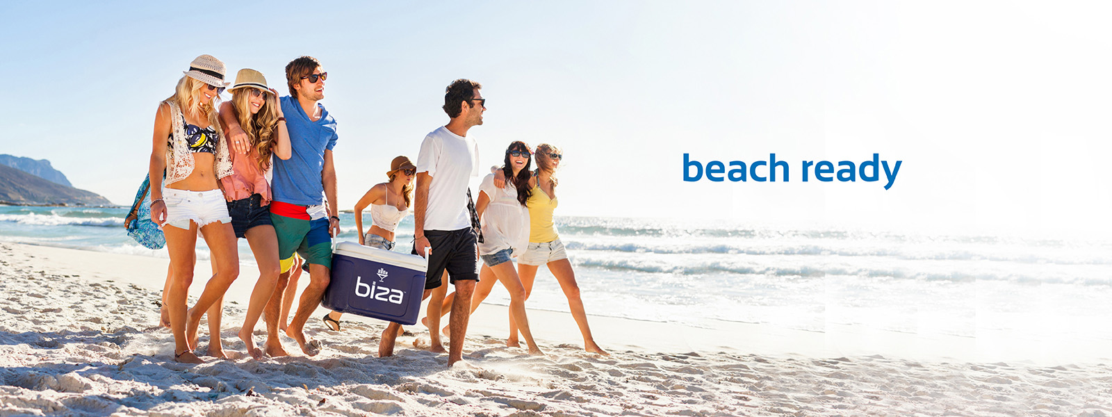 Group of friends walking on the beach smiling and laughing, carrying a cooler.