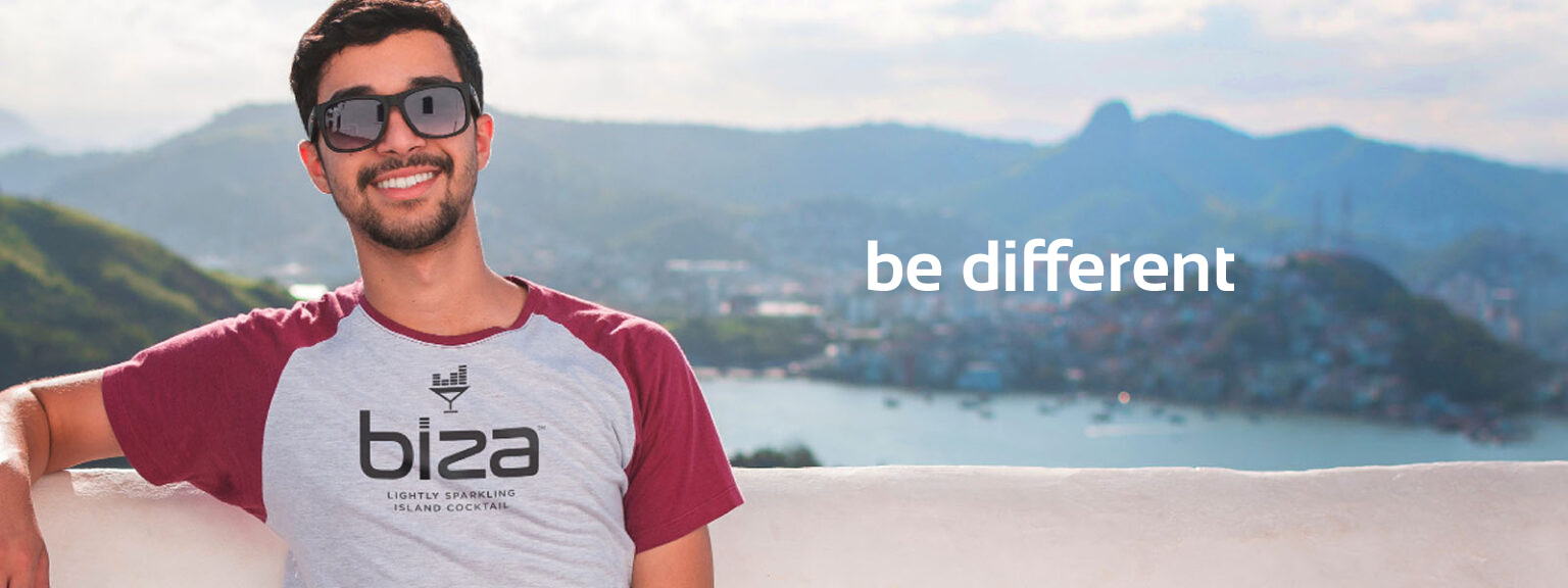 Guy with sunglasses and t-shirt that has the Biza logo on it, sitting with a beautiful scenery behind him.