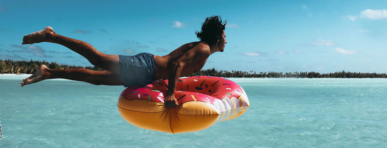 Guy jumping into the ocean with a donut inner tube.